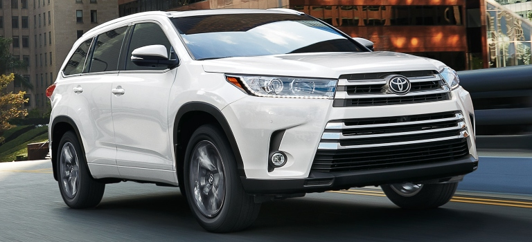 2019 Toyota Highlander in Blizzard Pearl traveling on the road front view