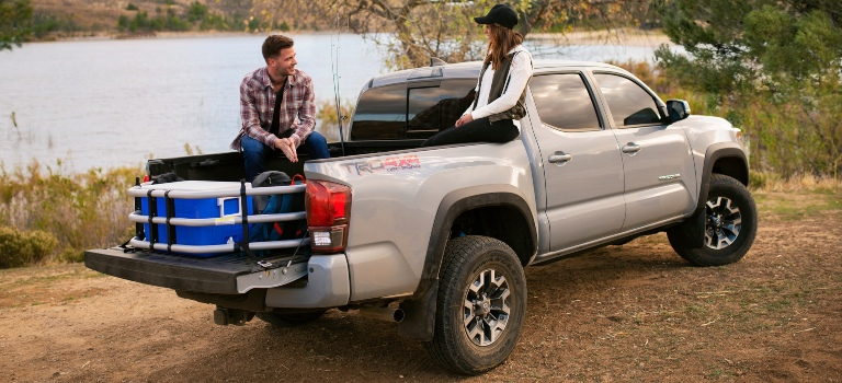 2019 Toyota Tacoma silver side back view on a trip with people in the bed
