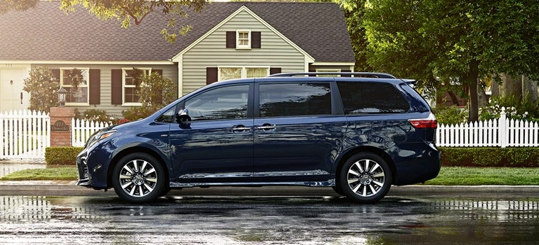 2020 Toyota Sienna blue side view on a wet road