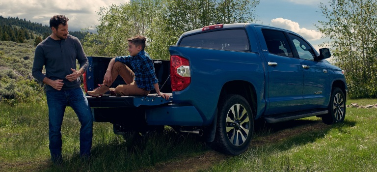 2020 Toyota Tundra blue back view tailgate open with kid