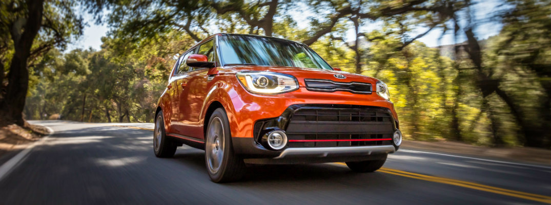 Orange-colored Kia Soul driving down a tree-lined road