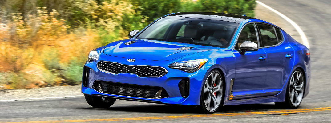 Blue 2018 Kia Stinger cruising down an rural road