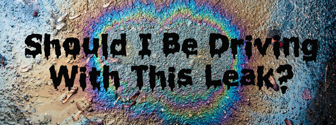 """Rainbow-colored oil slick on the ground with """"Should I Be Driving With This Leak?"""""""
