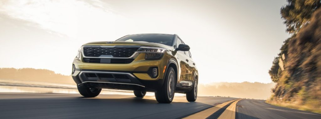 Low-angled image of a yellow 2021 Kia Seltos driving down a lakeside road