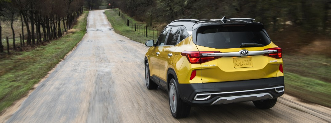 2021 Kia Seltos yellow exterior rear driving down country road