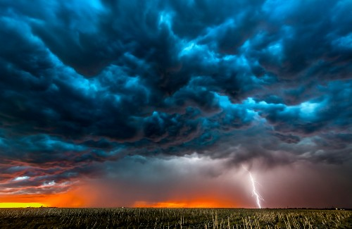 plain fields with dark storm clouds in sky and lightning