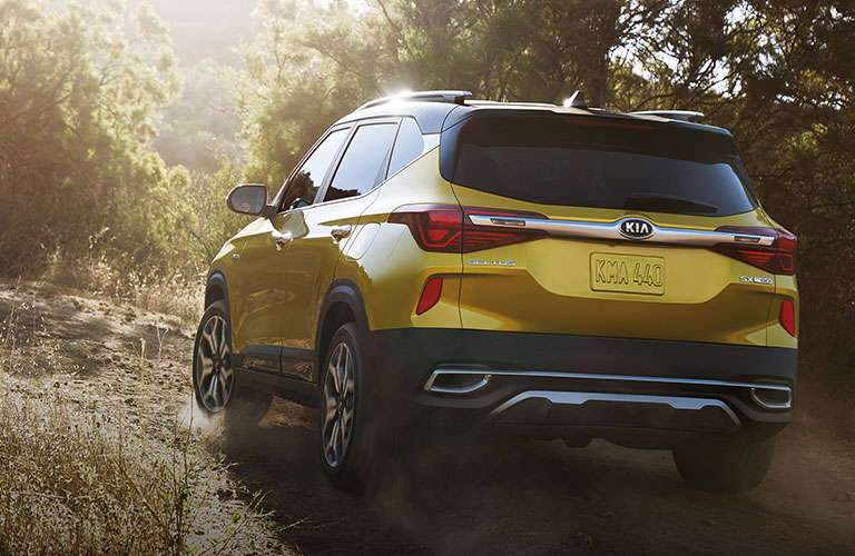 A yellow-colored 2021 Kia Seltos driving on a road surrounded by woods with the rear and left side exterior visible
