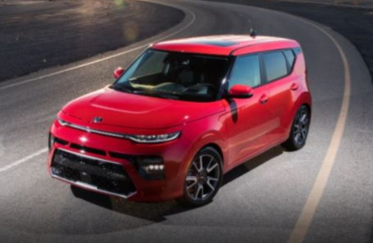 A red 2021 Kia Soul driving on a curved roadway