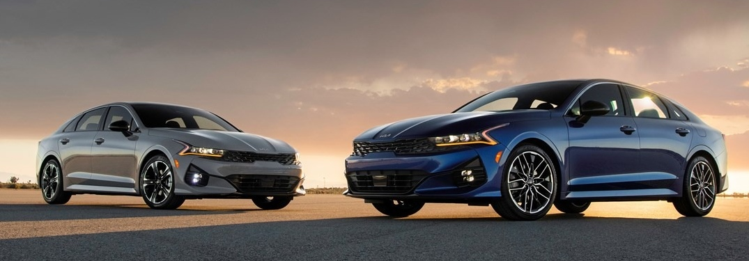 Two 2022 Kia K5 sedans with sunset in the background