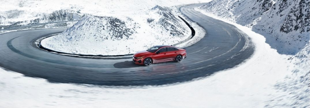 2022 Kia K5 driving through a road filled with snow