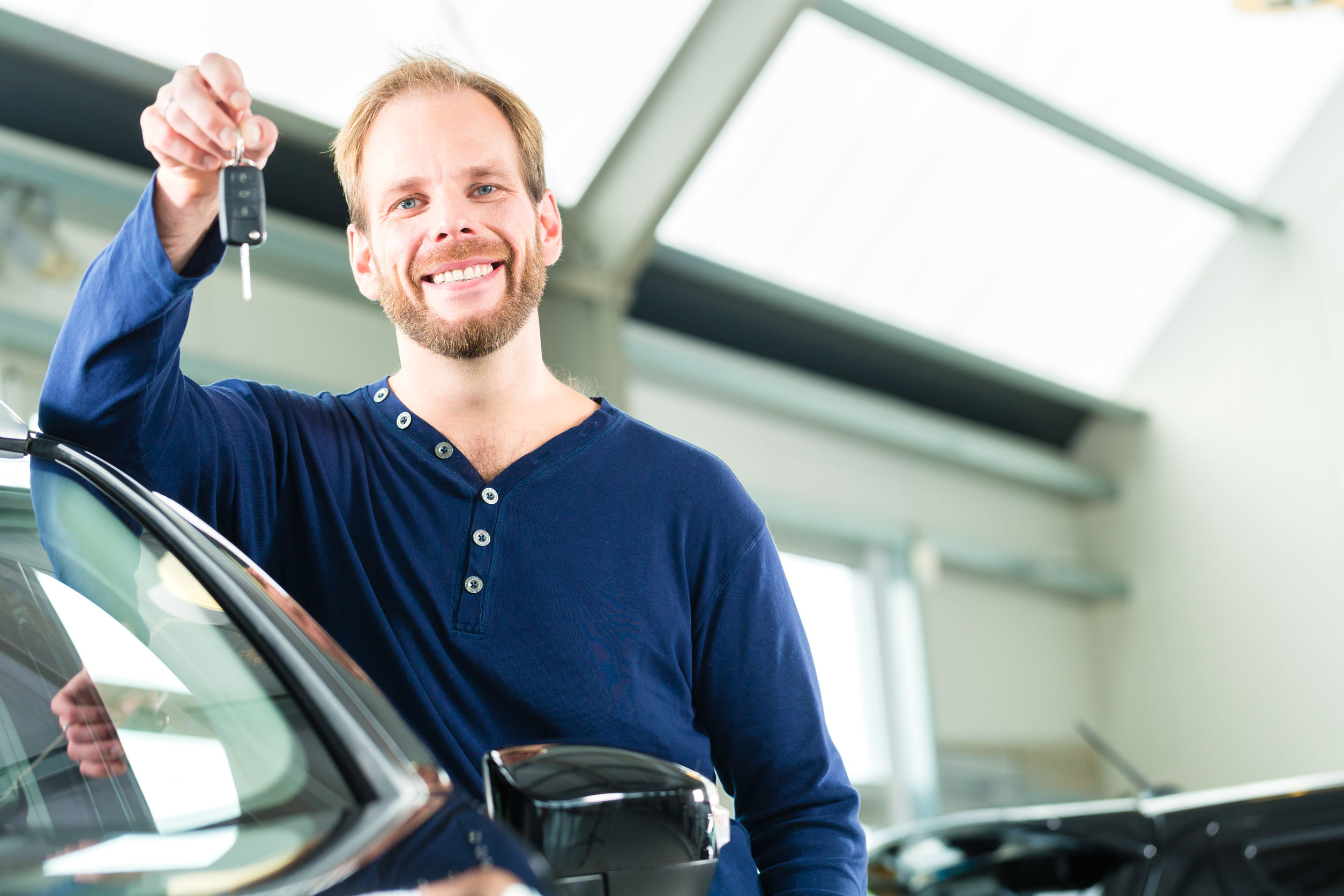 Man holding up keys to a new car