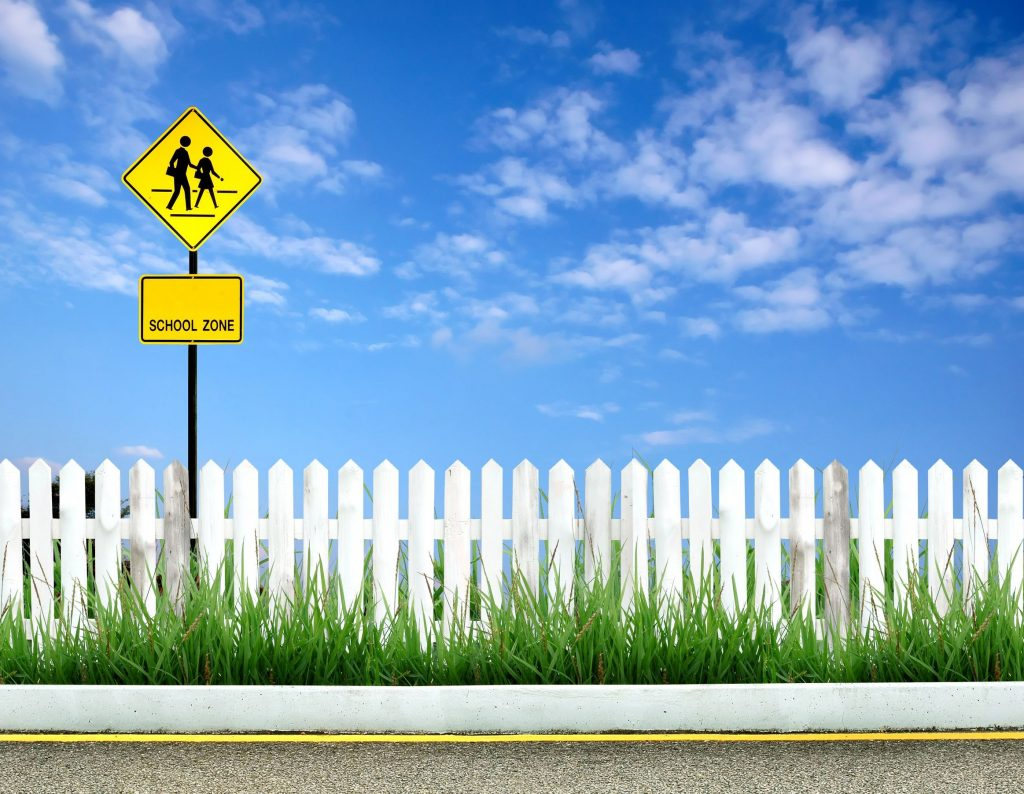 School zone sign against a blue sky and white picket fence