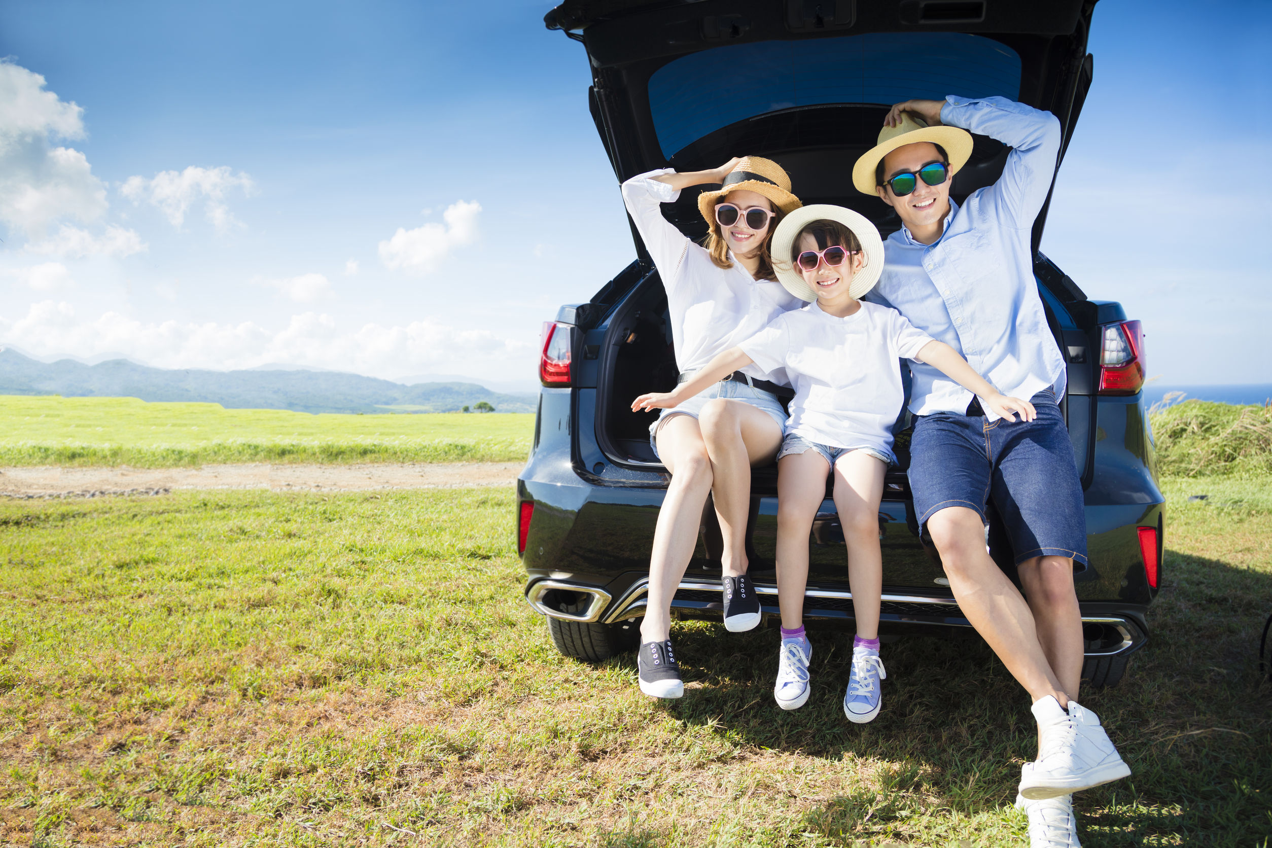 Smiling family sitting in the trunk of their SUV on a roadtrip