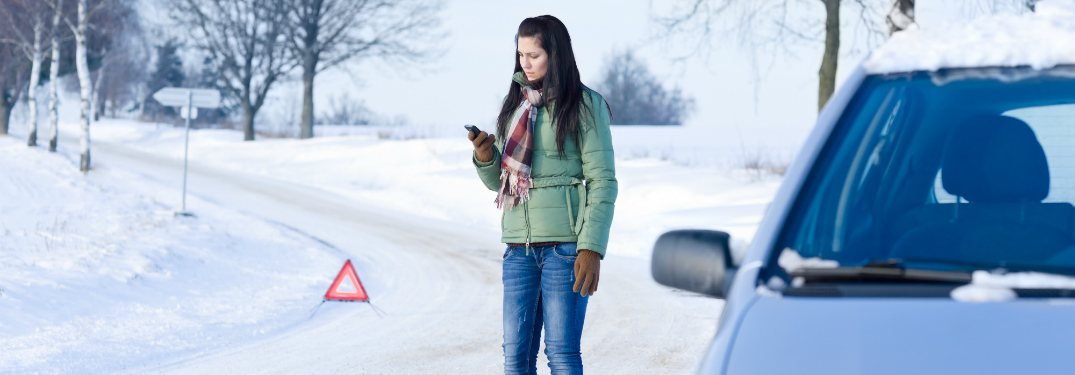 woman calling for help while car is broken down on the side of a snowy road