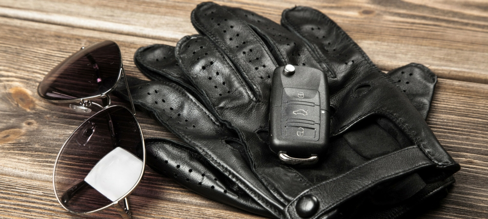 A car keyfob placed on top of black driving gloves next to a pair of sunglasses in a blog post about car gifts