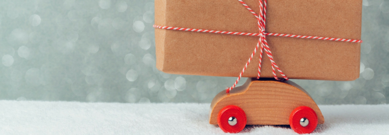 A toy car with a box tied to the top of it featured in a blog post about car gifts