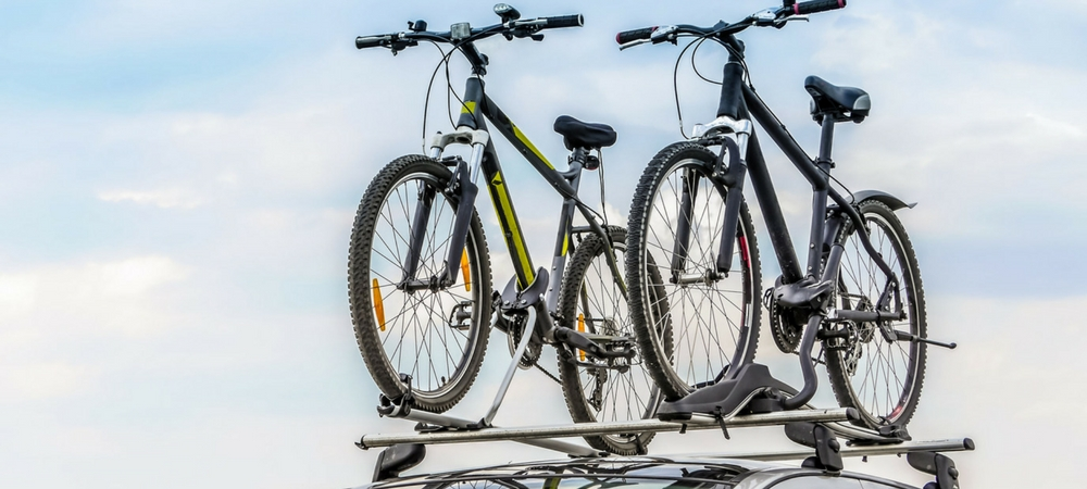 Two bikes attached to a car's carrier bars in a blog post about car gifts