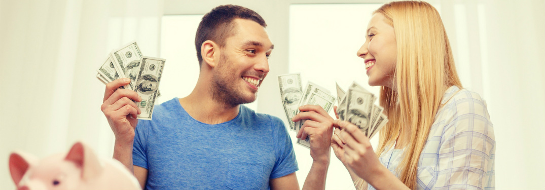 young man and woman holding money