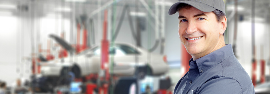 Auto technician smiling in front of body shop