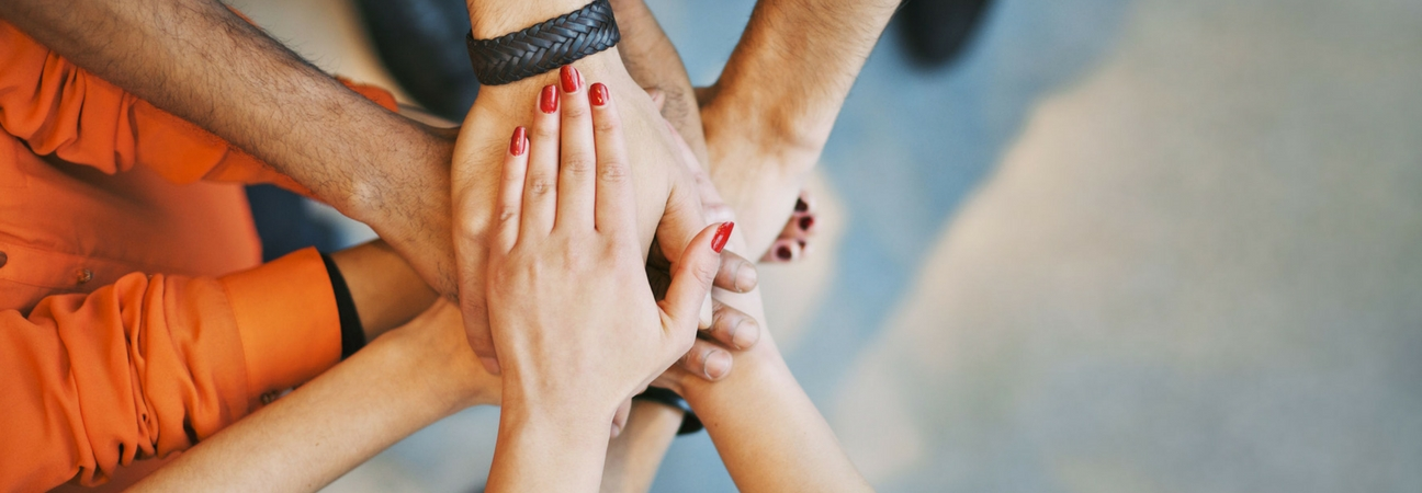 A group of hands stacked on top of each other for a cheer in a blog post about community involvement