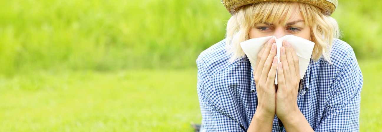 A woman blowing her nose into a tissue featured in a blog post about spring allergy driving tips