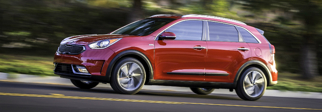 red 2018 kia niro driving on country road