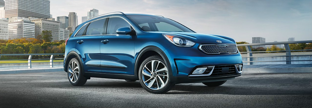 2018 Kia Niro in blue parked in an empty lot near water