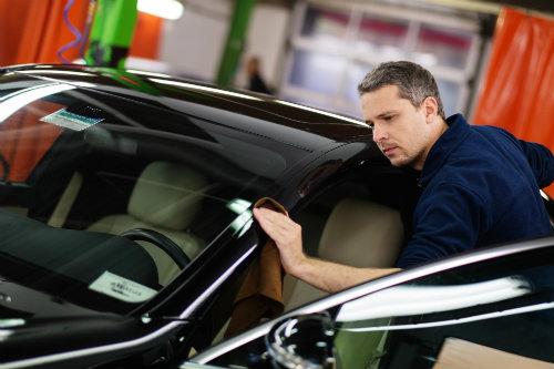 A mechanic polishing a car