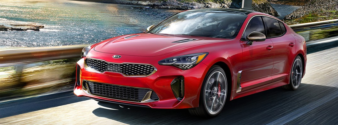 Red 2019 Kia Stinger model driving on waterfront road