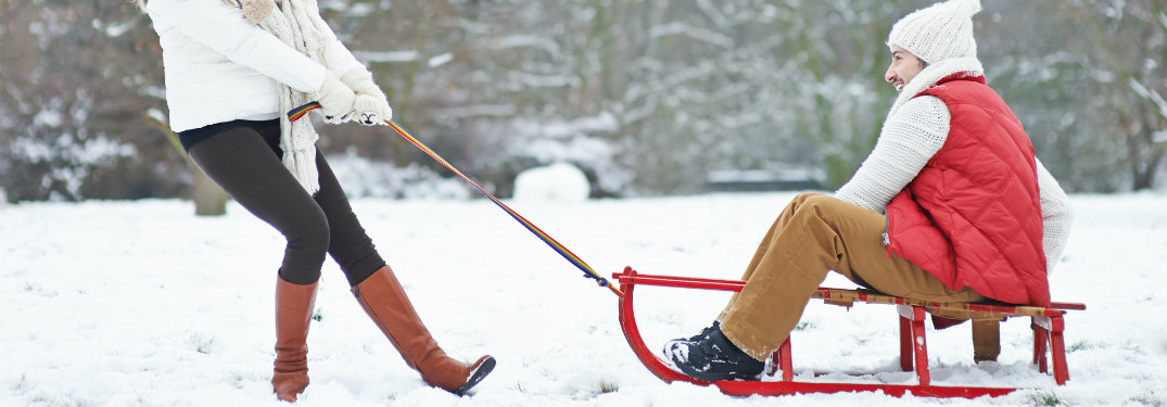 woman pulling a man on a sled, both having fun