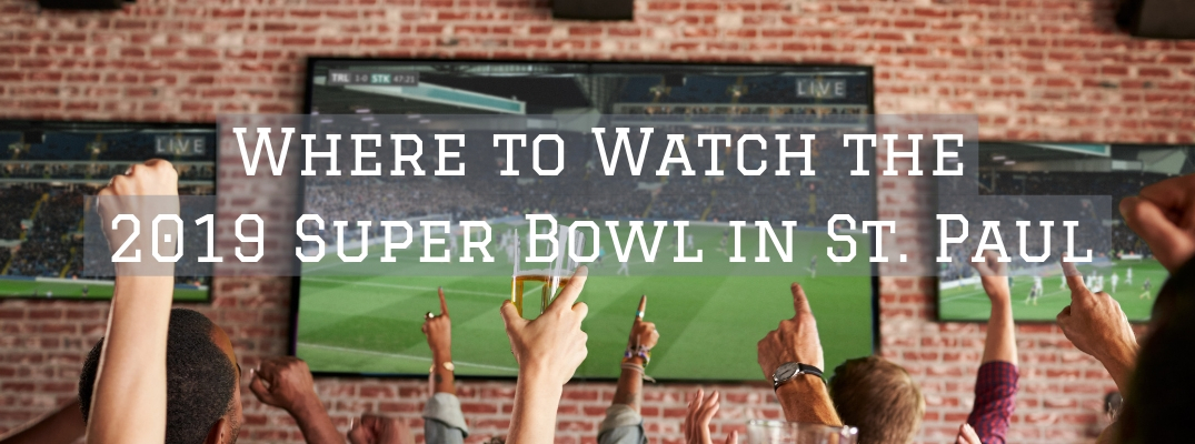 Hands cheering in front of football on tv screen with Where to Watch the 2019 Super Bowl in St. Paul white text