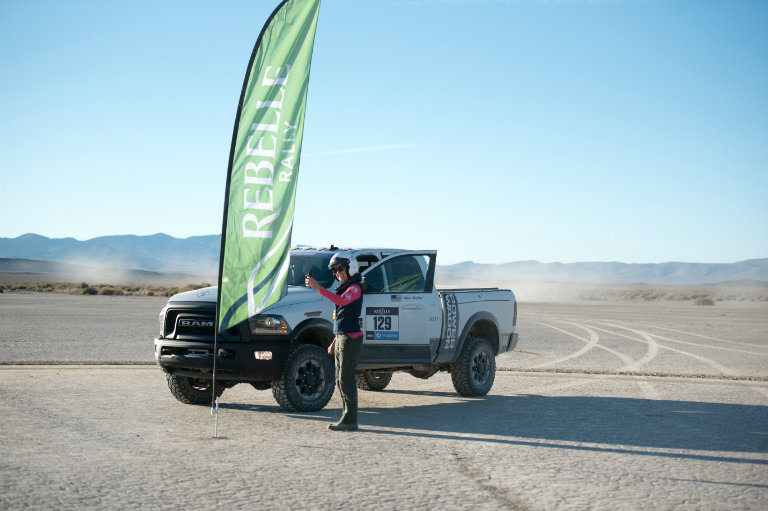 2017 Ram Power Wagon and driver or navigator in front of a Rebelle Rally flag