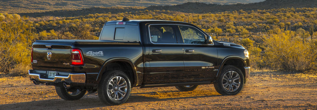 side and rear view of the 2019 Ram 1500 driving through a dry landscape