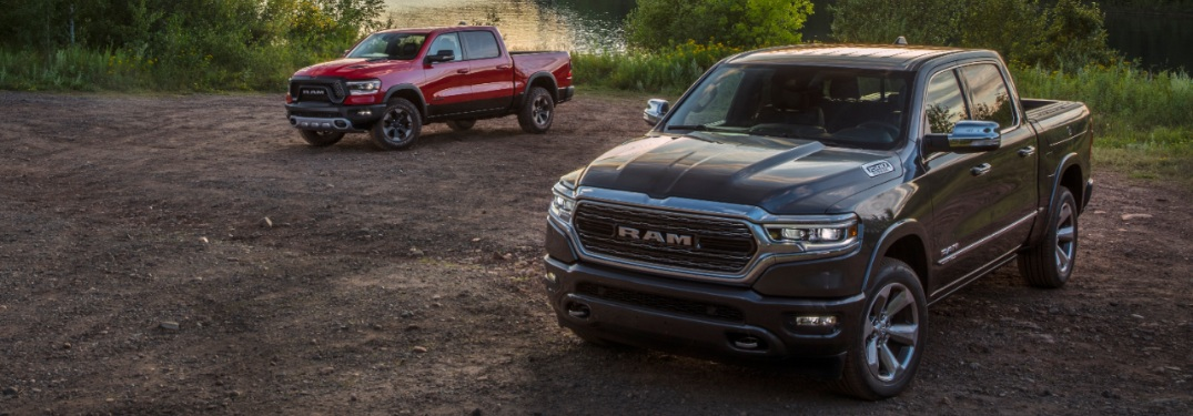 two 2020 Ram 1500 trucks by water's edge