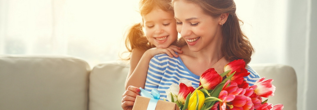 mom and daughter with flowers and gift for mother's day