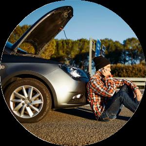 man stranded sitting by car