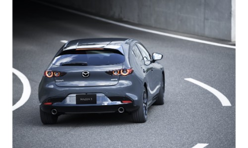 2019 Mazda3 exterior rear shot of the redesigned model with new bumper and taillights driving under a bridge