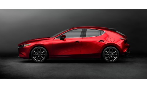 2019 Mazda3 hatchback exterior side shot with red paint color parked in a blank black showroom