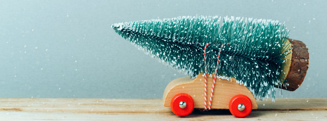 a wooden toy car with a tiny, snowy Christmas tree decoration tied to its roof