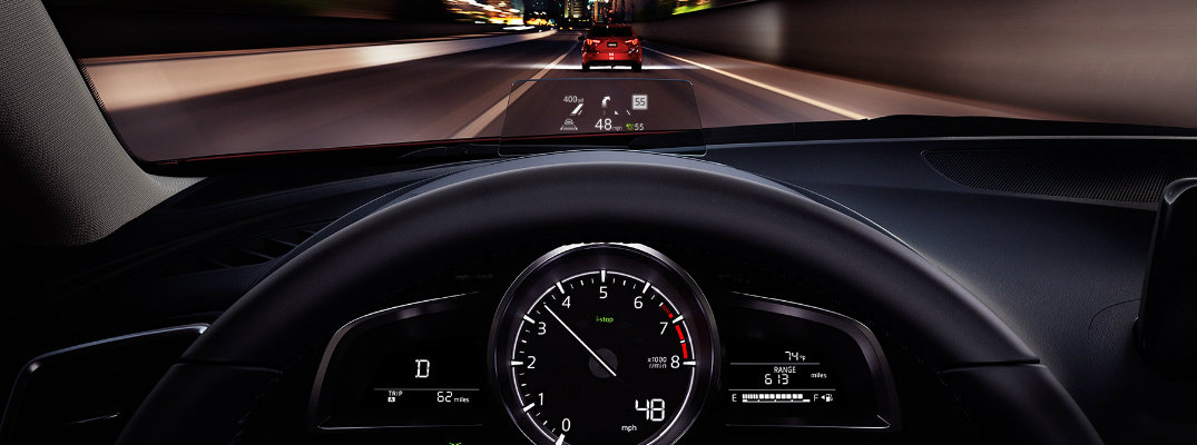 2018 Mazda3 sedan interior view from driver's seat of dashboard and active driving display while on the road at night