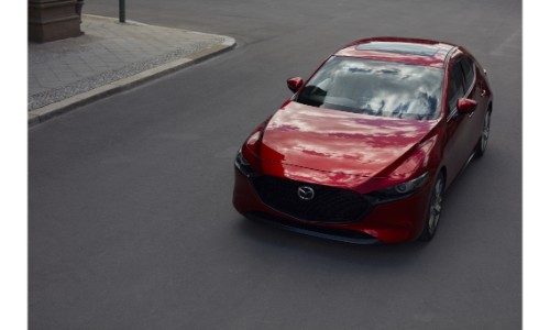 2019 Mazda3 Hatchback exterior overhead shot with red paint color parked in the middle of an empty street