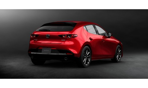 2019 Mazda3 Hatchback exterior rear shot with red paint color of back bumper and fascia design inside a black empty showroom