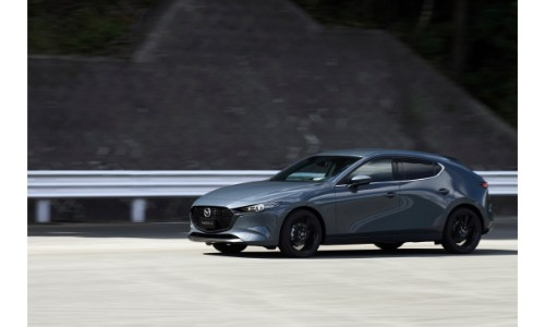 2019 Mazda3 Hatchback exterior shot with gray metallic paint color parked near metal railing