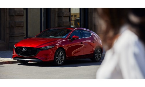 2019 Mazda3 Hatchback exterior shot with red paint color in the background as a woman in a white shirt in the foreground looks at it