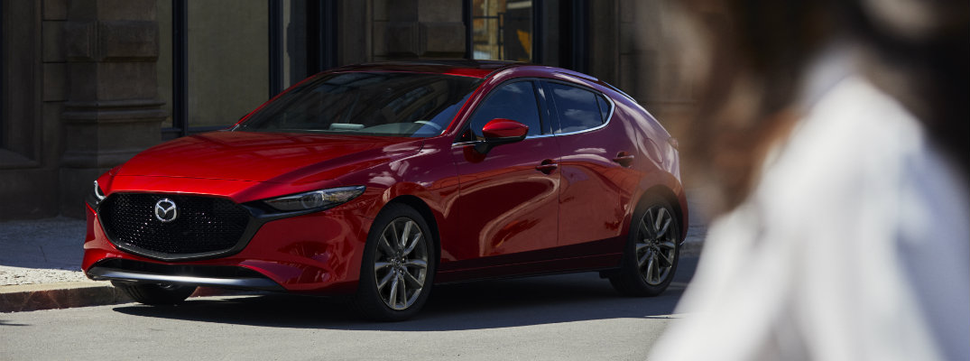 2019 Mazda3 hatchback exterior shot with red paint color parked in the background as a woman looks at it in the foreground