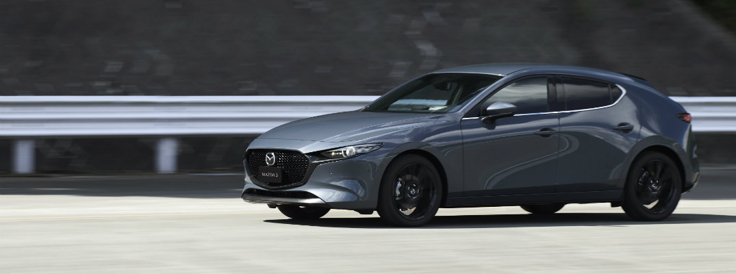 2019 Mazda3 hatchback exterior side shot with gray paint color parked on an empty lot next to metal railing