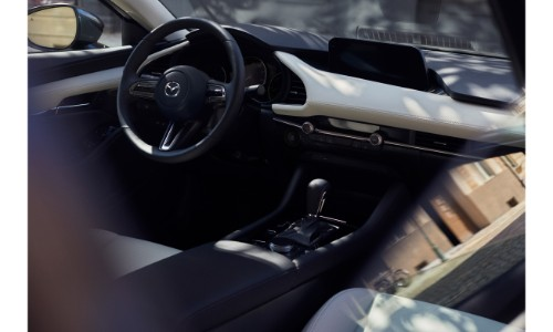 2019 Mazda3 interior shot of dashboard, steering wheel, and shift knob with white accent trimming