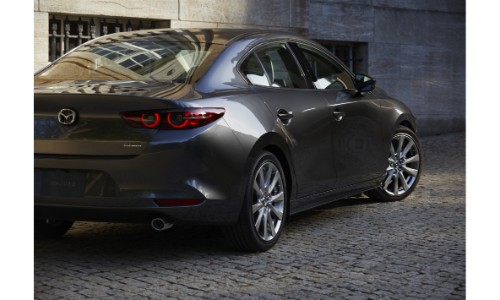 2019 Mazda3 sedan exterior rear shot with gray metallic paint color parked on a stone tiled road