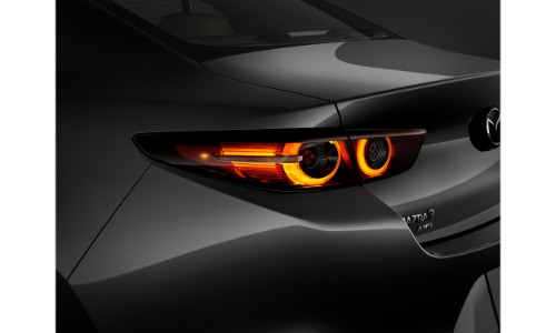 2019 Mazda3 sedan exterior shot with gray metallic paint color close up of new taillight redesign