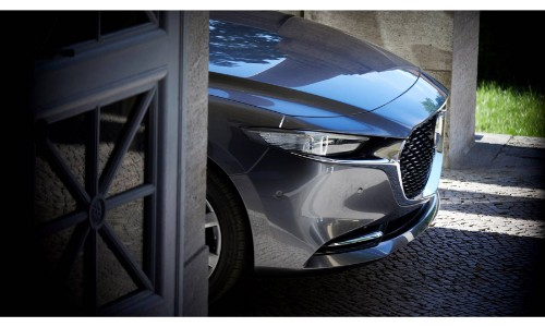 2019 Mazda3 sedan exterior shot with gray metallic paint color close up side shot of headlights and grille